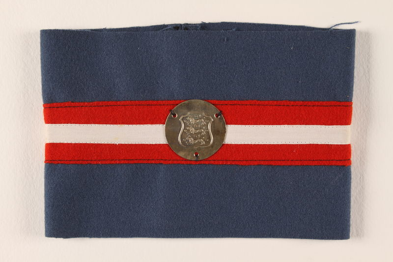 1995.111.1 front Blue armband with red and white stripes and a royal coat of arms medallion worn by a Danish resistance fighter