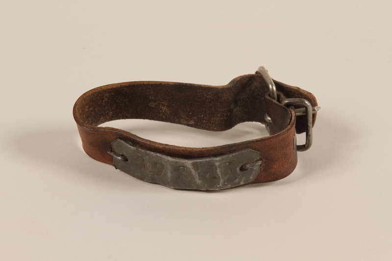 1989.188.1 front Leather ID bracelet with tag worn by a concentration camp inmate