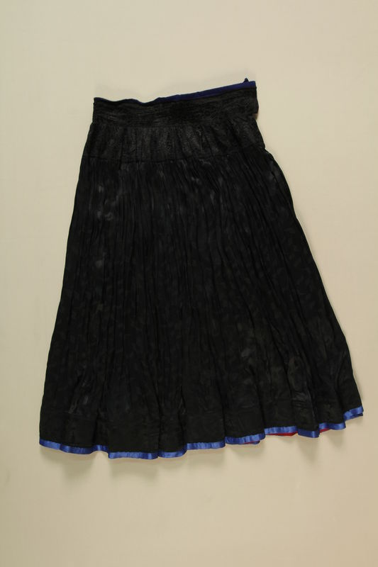 1995.13.1 front Black on black floral design cotton sateen skirt worn by a Romani woman
