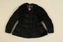Black jacket with plastic buttons worn by a Romani woman
