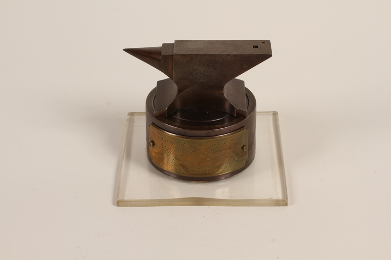 1989.259.1 front Anvil-shaped paperweight given to a US soldier serving as a displaced persons camp administrator