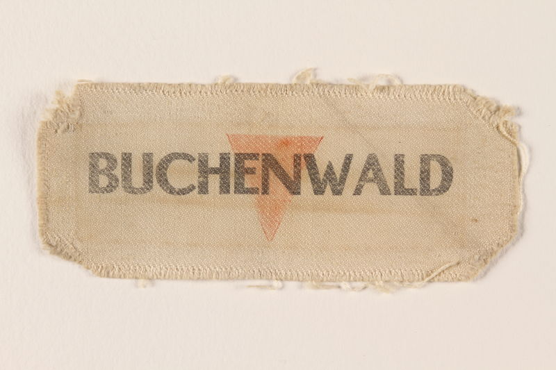 1995.78.5 front Cloth patch printed Buchenwald over a red inverted triangle worn by a German Jewish man
