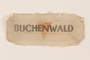 Cloth patch printed Buchenwald over a red inverted triangle worn by a German Jewish man