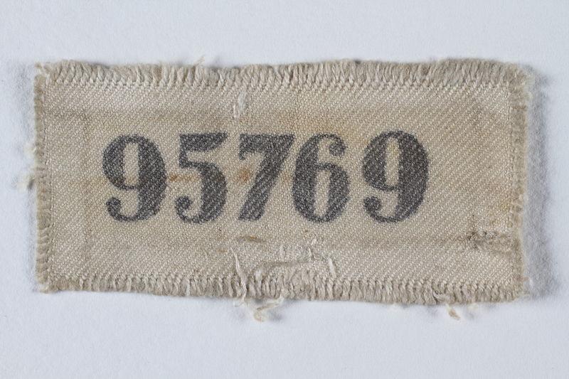 1995.78.6 front Prisoner ID badge number 95769 worn by a German Jewish man