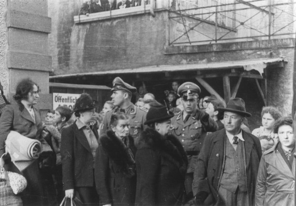 Two SS officers stand among a group of Jews waiting to board trucks during a deportation action in Loerrach.