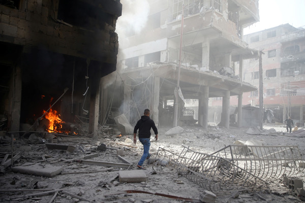 A man walks on rubble at a damaged site after an air strike on February 9, 2018, in the besieged town of Douma in the Eastern Ghouta area of Damascus, Syria. <i>Bassam Khabieh/Reuters</i>