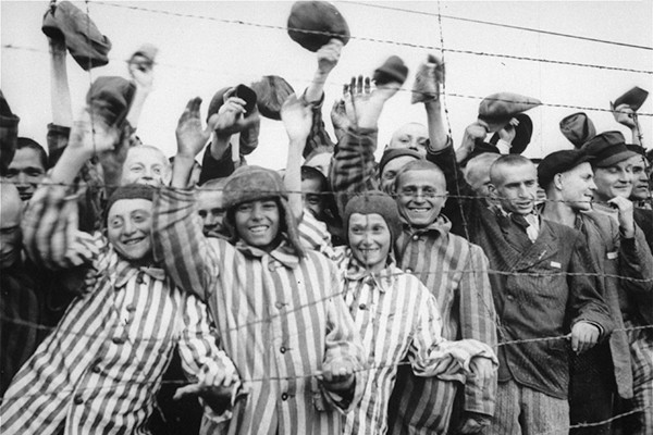 Survivors at the Dachau concentration camp cheer the arrival of American liberators in April 1945. <i>US Holocaust Memorial Museum, courtesy of National Archives and Records Administration, College Park</i>