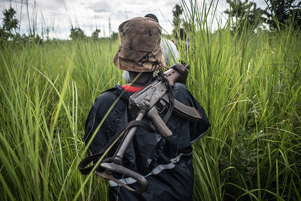 A SPLA-In Opposition soldier walks with her weapon through the elephant grass in rebel-held Magwi county of South Sudan's Eastern Equatoria state on August 28, 2017. <i>Jason Patinkin/US Holocaust Memorial Museum</i>