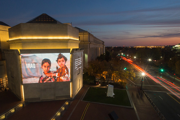A photograph by Mackenzie Knowles-Coursin of Yezidi sisters living in a camp for internally displaced persons in Dohuk, Iraq, is projected during FotoWeek 2015. <i>US Holocaust Memorial Museum</i>
