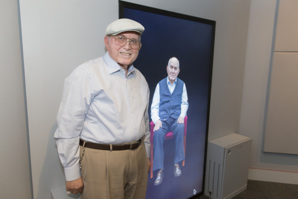 """Holocaust survivor Pinchas Gutter stands before a video display showing his testimony. In this """"New Dimensions in Testimony"""" installation, displayed in cooperation with the USC Shoah Foundation, Museum visitors were able to ask questions that would be answered by Gutter's previously recorded words. <i>US Holocaust Memorial Museum</i>."""