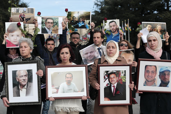 During peace talks in Geneva in February 2017, Syrians hold images of loved ones disappeared by Syrian government forces over the course of the six-year war. <i>Dylan Collins</i>