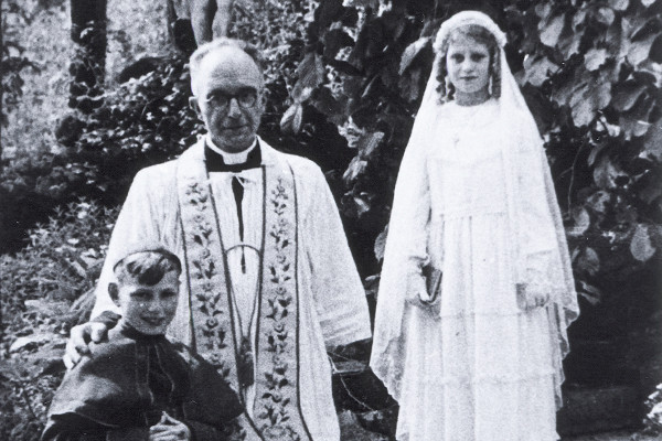 Beatrice Muchman while in hiding wearing her first communion dress.  She is standing next to Father Vaes and her cousin Henri who is a choir boy. <i> US Holocaust Memorial Museum, courtesy Beatrice Muchman.</i>