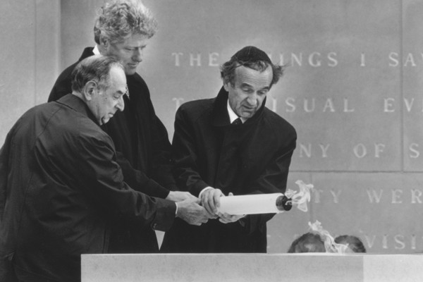 At the Museum's dedication in April 1993, Elie Wiesel (right) lights the eternal flame with President Bill Clinton and and Museum Chairman Harvey Meyerhoff (left). <i>Agence France Presse</i>