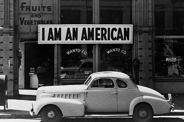 "The Japanese American owner of this Oakland, California, store hung a sign reading ""I am an American"" on December 8, 1941—the day after Japan bombed Pearl Harbor. The store was closed in March 1942 following orders to persons of Japanese descent to evacuate from certain West Coast areas. <i>Dorothea Lange/Library of Congress</i>"
