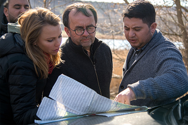 Lara Logan, Father Patrick Desbois, and Serban Catalin, a translator, look at a map of mass gravesites in Moldova. <i>Courtesy of Kate Kornberg/Yahad - In Unum</i>