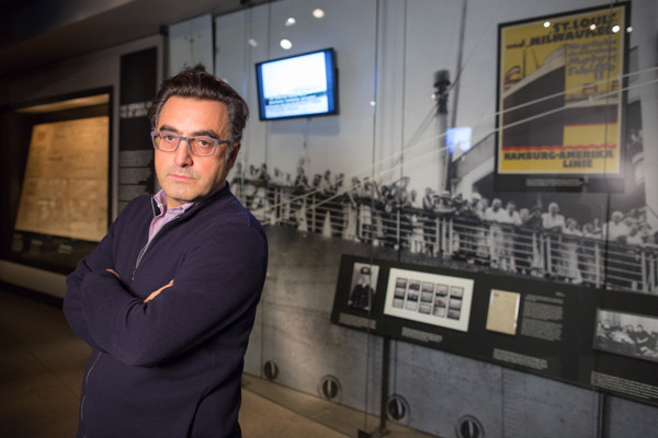 Maziar Bahari stands in front of a display in the Museum's Permanent Exhibition about the Jewish refugees aboard the MS St. Louis, the subject of his 1994 documentary. <i>US Holocaust Memorial Museum</i>
