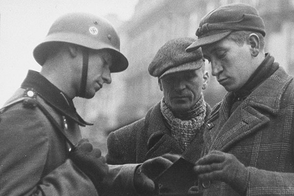 A German police guard inspects the papers of two Jewish men at a gate to the Warsaw ghetto in 1941. <i>US Holocaust Memorial Museum, courtesy of bpk-Bildagentur</i>